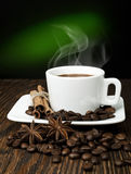 Coffee. Hot coffee on a saucer with spices on a wooden table Royalty Free Stock Photography