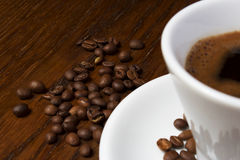 Coffee. A cup of fresh black coffee against background of roasted coffee beans Royalty Free Stock Photo