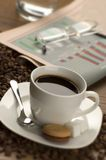 Coffee. Cup of hot coffee with newspaper and glasses in the back Royalty Free Stock Image
