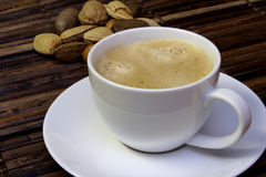 Coffee. Cup of coffee with nuts in background Royalty Free Stock Photo