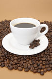 Coffee. White coffee cup with coffee beans on brown background stock images