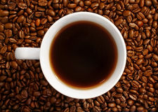 Coffee. A cup of coffee among coffee beans Stock Photo
