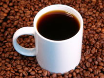 Coffee. A hot cup of coffee surrounded by whole coffee beans royalty free stock images