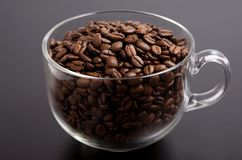 Coffee. Cup of roasted coffe beans on black background stock images