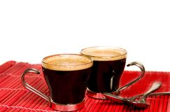 Coffee. Two glass cups of coffee on a red bamboo tablecloth against white background Stock Images