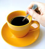 Coffee #9. A cup of black coffee, hand stirring sugar royalty free stock image
