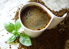 Coffee. Cup with basil leaflets on top stock image