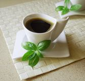 Coffee. Cup with basil leaflets on top royalty free stock photography