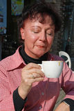 Coffee addict. A middle age woman drinking coffee in a sidewalk cafe Stock Photo