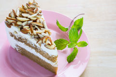 Coffee almond cake delicious with green mint  on dish. Royalty Free Stock Photo