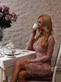 Coffee alone. Tense blonde drinking coffee alone in a restaurant, frustrated and angry for waiting Royalty Free Stock Photos