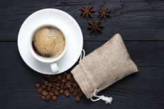 Coffee with anise on a black background and a bag of coffee beans Royalty Free Stock Photos