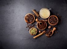 Coffee, anise, cinnamon and nutmeg on black background. Top view royalty free stock photo
