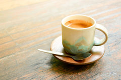 Coffee in antique ceramic cup on wooden table Royalty Free Stock Photography
