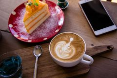 Coffee aroma latte art cup and tasty christmas cake on wood table relaxtime in cafe coffee shop royalty free stock photography