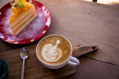 Coffee aroma latte art cup and tasty christmas cake on wood table relaxtime in cafe coffee shop royalty free stock images