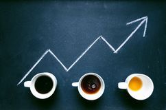 Coffee and arrow from coffee beans. Move up of energy. Trend up of energy. Arrow and graph. Coffee on a blackboard. Concept of ene stock photo