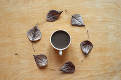 Coffee and autumn leaves on wood Stock Photography