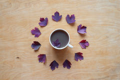 Coffee and autumn leaves on wooden background Royalty Free Stock Photography