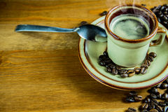 Coffee background. Coffee beans on a wooden table, a cup of espresso coffee and a steel spoon Stock Photo