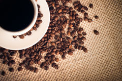 Coffee Background with a Cup & Roasted Beans. White coffee cup on a coffee bean background. Everything is placed on a brown fabric cloth giving a warm feeling to Stock Images