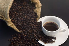 Coffee bag and cup. Burlap bag with a stream of coffee beans on a coffee cup with espresso Royalty Free Stock Photo