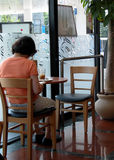 Coffee bar. A woman in a coffee bar sitting and reading a magazine Royalty Free Stock Images