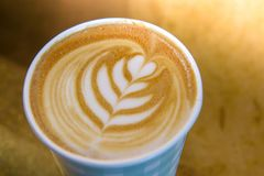 Coffee Barista holding a take away cup with milk foam in a leaf shape. Image stock photos