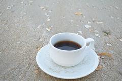 Coffee on the beach. Place one cup of black coffee on the sand with shells on the sand Stock Photography