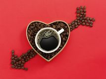 Love Coffee Cup. Coffee bean arrow and heart with a cup of fresh black coffee on red background Stock Photography