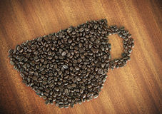 Coffee bean as a cup on wooden table Royalty Free Stock Images