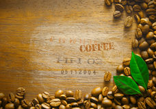 Coffee bean background border. On a textured wooden surface with stamped text COFFEE and consignement numbers from the original shipment of beans stock photo