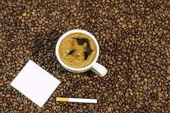 Coffee bean background with cup of fresh hot coffee and cigar with white card. Close royalty free stock photo