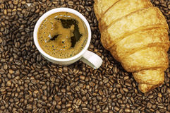 Coffee bean background with cup of fresh hot coffee and croissant Stock Image