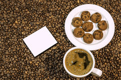 Coffee bean background with cup of fresh hot coffee and plate full of cookies Royalty Free Stock Photo