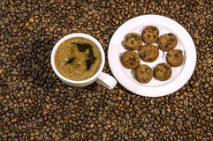 Coffee bean background with cup of fresh hot coffee and plate full of cookies Stock Image