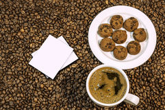 Coffee bean background with cup of fresh hot coffee and plate full of cookies Royalty Free Stock Photography