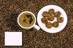 Coffee bean background with cup of fresh hot coffee and plate full of cookies Royalty Free Stock Image