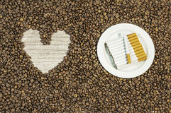 Coffee bean background with heart and many cigars on white plate Royalty Free Stock Image