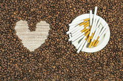 Coffee bean background with heart and many cigars on white plate Stock Images