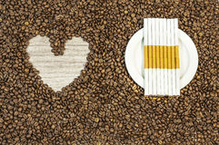 Coffee bean background with heart and many cigars on white plate Royalty Free Stock Photos