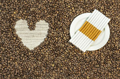 Coffee bean background with heart and many cigars on white plate Stock Photos