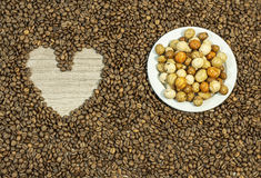 Coffee bean background with heart and plate full of various peanuts. Close Stock Photo