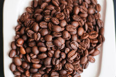 Coffee bean. S on a white saucer on a dark background Royalty Free Stock Images