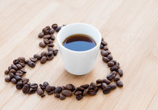 Coffee bean and black coffee inside a heart Royalty Free Stock Photography