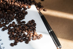 Coffee bean. Coffee bean and black pen on brown paper stock photo