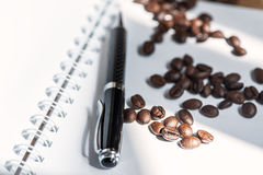 Coffee bean. And black pen on white paper book royalty free stock photography