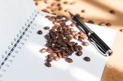 Coffee bean. And black pen on white paper book royalty free stock photos