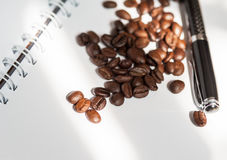 Coffee bean. And black pen on white paper book royalty free stock images