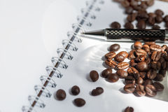 Coffee bean. Coffee bean and black pen on white paper book royalty free stock images